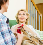 Woman visiting  sick friend and giving her a linctus Royalty Free Stock Photos