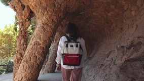 Woman visits historic places in Barcelona. Back view of a woman with backpack walking and looking at landmarks of Spain on vacation, Historic architecture. Park stock video footage
