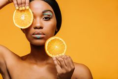 Woman with vivid makeup and orange slices. Close up of woman with vivid makeup and orange slices in hand. Female model with copy space over yellow background Royalty Free Stock Photo