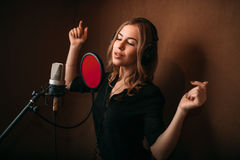Woman vocalist in headphones against microphone Stock Photography
