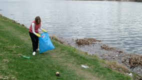 Woman volunteer cleaning up the trash by the river. Picking up garbage outdoors. Ecology and environment concept stock video footage