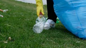 Woman volunteer cleaning up the trash by the river. Picking up garbage outdoors. Ecology and environment concept stock footage