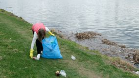 Woman volunteer cleaning up the trash by the river. Picking up garbage outdoors. Ecology and environment concept stock video