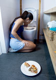 Woman vomiting and throwing up kneeling on floor of toilet WC guilty after eating pizza Stock Image