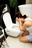 Woman vomiting in toilet. Beautiful adult woman vomiting in toilet Royalty Free Stock Image