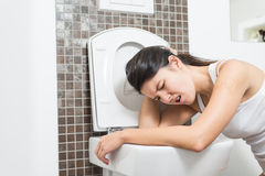 Woman vomiting into the toilet bowl. Young woman vomiting into the toilet bowl in the early stages of pregnancy or after a night of partying and drinking Royalty Free Stock Photography