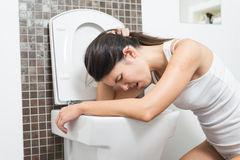 Woman vomiting into the toilet bowl. Young woman vomiting into the toilet bowl in the early stages of pregnancy or after a night of partying and drinking Stock Photography