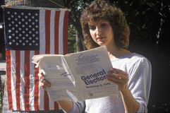 Woman voter. Reading election pamphlet at the entrance to a polling place, CA Royalty Free Stock Photography