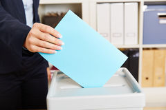 Woman voting with ballot paper on box Royalty Free Stock Photo