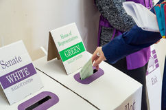 Woman voting on 2016 federal election day in Australia. Melbourne, Australia - July 2, 2016: a woman placing a ballot paper in a ballot box on 2016 federal Royalty Free Stock Images