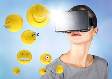 Woman in VR with emojis and flares against blue background stock illustration