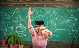 Woman in VR glasses. Confident woman in virtual reality headset pointing in air. Modern education. Back to school. Virtual education. Virtual reality gadget royalty free stock image
