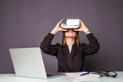 Woman in VR glasses. Confident young woman in virtual reality headset pointing in the air while sitting at her working place in of. Woman in VR glasses stock images