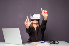 Woman in VR glasses. Confident young woman in virtual reality headset pointing in the air while sitting at her working place in of. Woman in VR glasses royalty free stock photos