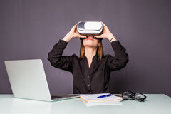 Woman in VR glasses. Confident young woman in virtual reality headset pointing in the air while sitting at her working place in of. Woman in VR glasses stock photo