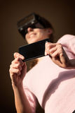 Woman with vr glasses and smartphone Stock Image