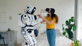 A woman in VR-glasses is touching a cyborg stock video