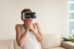 Woman in VR headset frightened because of realistic effects. Woman feeling scared or surprised when using VR glasses at home. Lady excited with effect of Stock Images