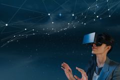 Woman in VR headset looking at stars against blue background. Digital composite of Woman in VR headset looking at stars against blue background Royalty Free Stock Images