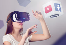 Woman in VR headset looking up and interacting with objects stock images
