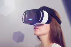 Woman in VR headset looking up at the objects in virtual reality. VR is a computer technology that simulates a physical presence and allows the user to stock images