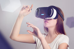 Woman in VR headset looking up and trying to touch objects. In virtual reality. VR is a computer technology that simulates a physical presence and allows the Royalty Free Stock Photos