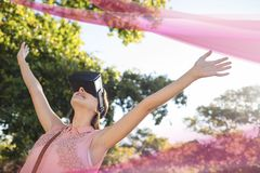 Woman in VR headset raising hands against background with pink lights and trees. Digital composite of Woman in VR headset raising hands against background with Stock Photo