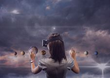Woman in VR headset touching 3D planets against purple sky with clouds and flares Royalty Free Stock Photography