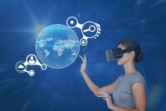 Woman in VR headset touching interface against blue background with flares. Digital composite of Woman in VR headset touching interface against blue background stock image