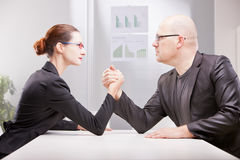 Woman vs man business arm wrestling. Busineee women facing business men and starting to perform an arm wrestling to decree who's best Stock Photography