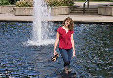 Woman Wading in Pond. With fountain in background Royalty Free Stock Images