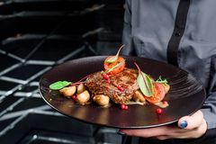 Woman waiter holding a dark round plate with grilled juicy steak with grilled mushrooms, tomatoes and cranberries. Close up. Space. Dark background royalty free stock photo