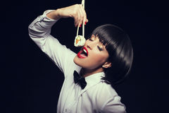 Woman in waiter style eat sushi Royalty Free Stock Photos