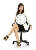 Woman waiting. Pretty smiling asian business woman waiting holding a clock Royalty Free Stock Photo