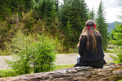 Woman waiting alongside a mountain. Road sitting on a fallen tree trunk with her back to the camera admiring the magnificent forested scenery Stock Photography