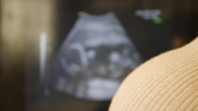 Woman waiting for the baby. Dark-haired pregnant girl on a monitor background with ultrasound video of a baby. Movable focus. Dark-haired woman with a big stock video footage