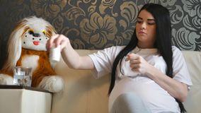 Woman waiting for the baby. Pregnant girl sitting on a white couch drinking vitamins with water from a glass. Dark-haired woman with a big belly in the room stock video