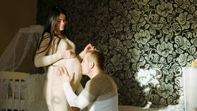 Woman waiting for the baby. A young man puts his head on and kisses the belly of his pregnant wife. A girl with dark hair is happy and wide smile. Young couple stock footage