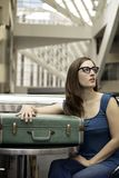 Woman waiting. A beautiful young woman waits with a vintage suitcase stock photo