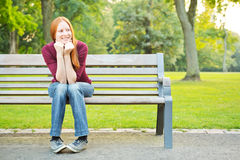 A Woman Waiting on a Bench in a Park Stock Image