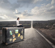 Woman waiting on a bench with a suitcase Stock Images