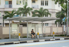 A woman waiting for the bus in Geyland, Singapore Stock Photography