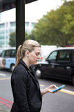 Woman waiting at bus stop with mobile phone in London Royalty Free Stock Photography