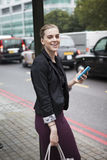 Woman waiting at bus stop with mobile phone in London Stock Images