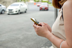 A woman is waiting for a cab. Using a smartphone royalty free stock photos