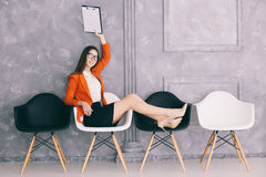 Woman waiting on the chair for decision of jon interview. Young happy woman waiting on the chair for decision of jon interview royalty free stock images