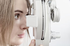 Woman waiting for eye examination with phoropter. Woman patient waiting for eye examination with phoropter at optometric clinic Royalty Free Stock Image