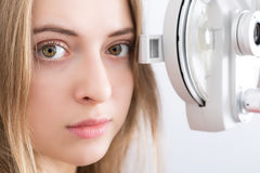 Woman waiting for eye examination with phoropter. Woman patient waiting for eye examination with phoropter at optometric clinic Stock Photo