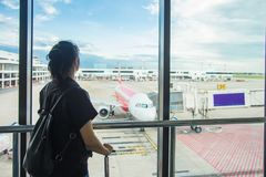 Woman waiting for a flight at the airport; window airport.Young woman in the airport, looking through the window at planes royalty free stock photo