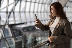 woman waiting for flight and using smart phone in airport royalty free stock images